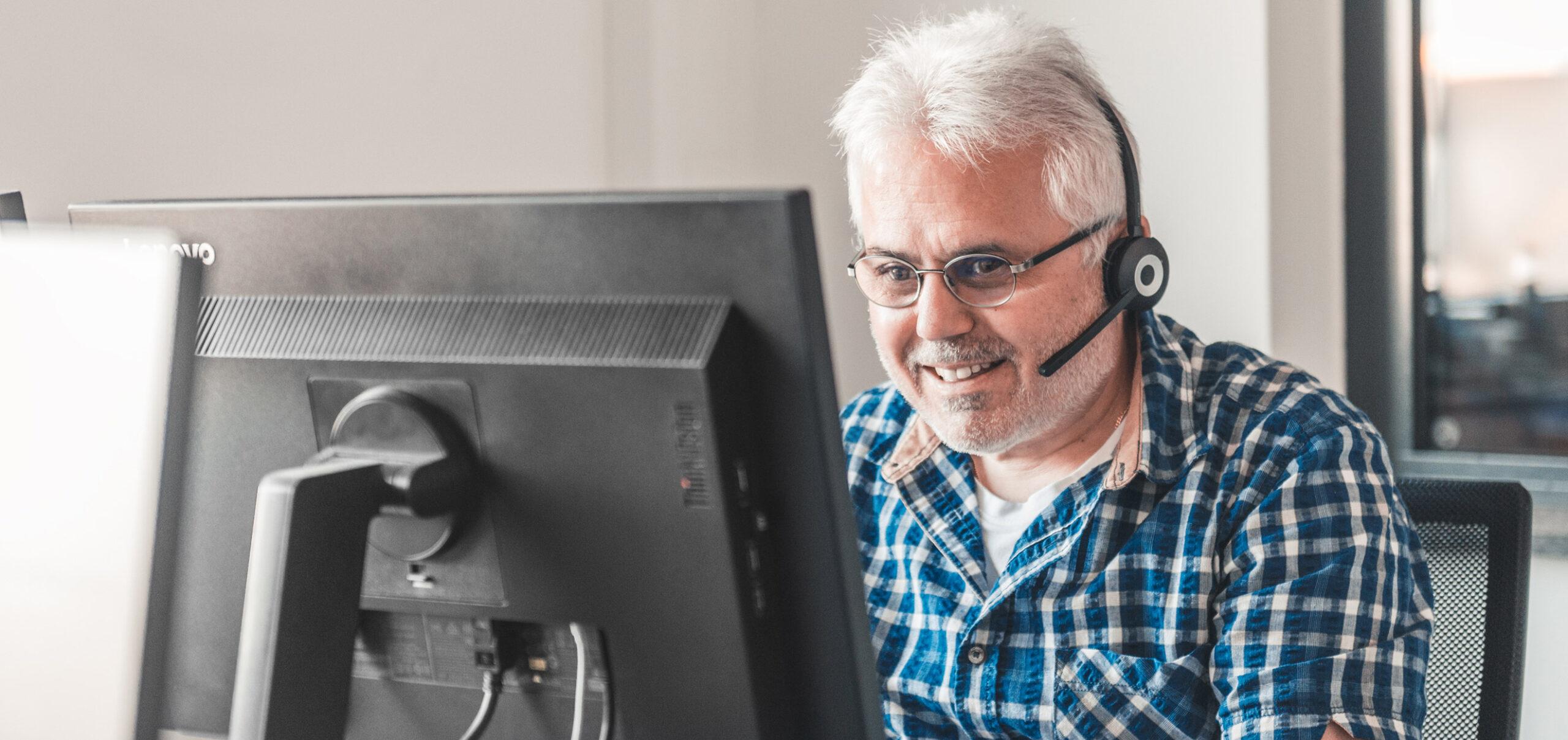 Mitarbeiter am PC mit Headset